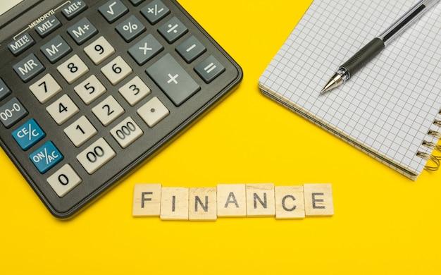 Word-financiën gemaakt met houten letters op gele en moderne rekenmachine met pen en notitieboekje.