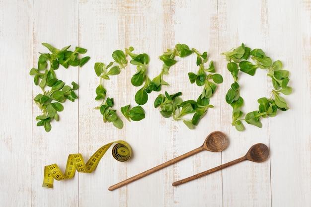 Word food van verse rauwe salade bladeren op lichte houten tafel. bovenaanzicht. kopieer ruimte.