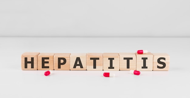Word hepatitis gemaakt met houten bouwstenen met rode pillen, medisch concept.