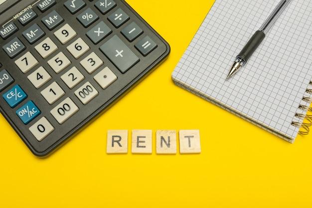 Word huur gemaakt met houten letters op gele en moderne rekenmachine met pen en notitieboekje.