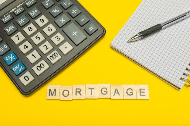 Word hypotheek gemaakt met houten letters op gele en moderne rekenmachine met pen en notitieboekje.