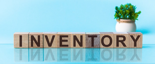 Word inventaris gemaakt met houten bouwstenen op een blu-achtergrond