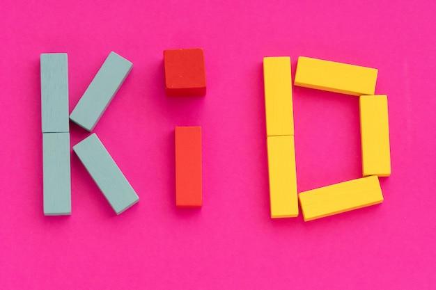 Word kid gemaakt van veelkleurig houten bakstenen speelgoed op paars papier