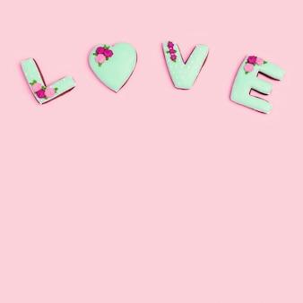 Word love door zelfgemaakte koekjes met zacht groen suikerglazuur op roze pastelkleur. vakantie wenskaart