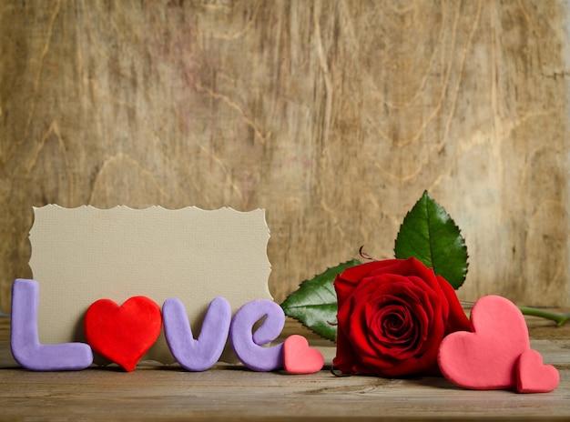 Word love samenstelling met lege kaart voor tekst op het oppervlak van de houten plank en harten handgemaakt rond roos in de buurt.