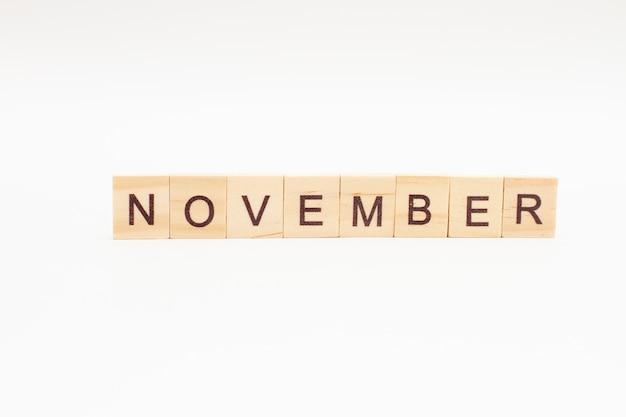Word november gemaakt van houten blokken geïsoleerd