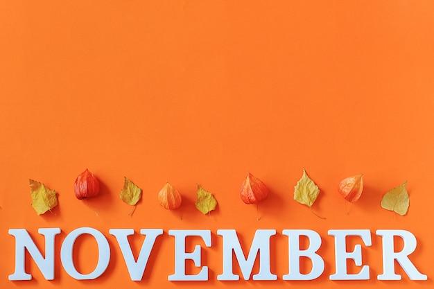 Word november van witte letters en heldere herfstbladeren herbarium op oranje papier achtergrond.