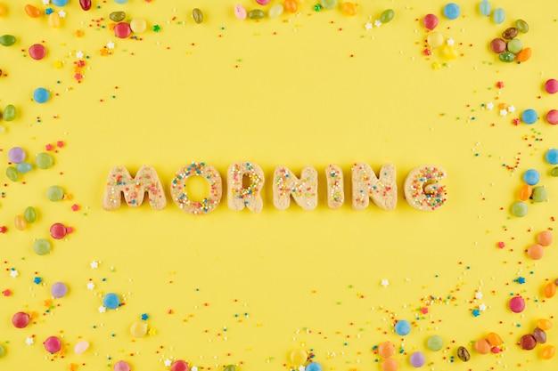 Word ochtend gerangschikt van zelfgemaakte koekjes alfabet op gele tafel met kleine zoete snoepjes en hagelslag
