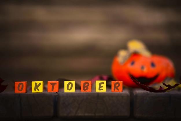 Word oktober op een achtergrond met pompoen