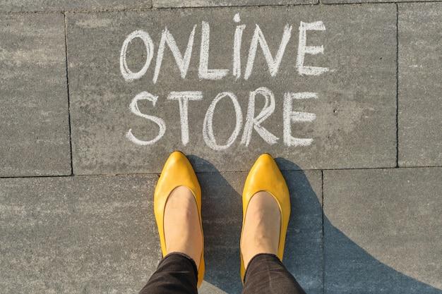 Word online winkel geschreven op grijze stoep met vrouwenbenen