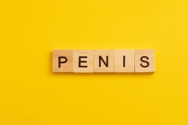 Word penis gemaakt van houten letters op gele achtergrond.