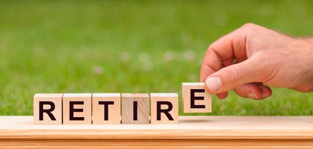 Word pensioen geschreven met houten blokken. man hand met houten kubus blok met pensioen