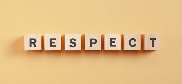 Word respect op houten kubussen.