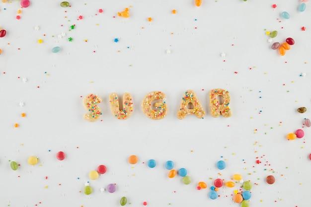 Word suiker gemaakt van cookie letters en regenboog hagelslag op witte achtergrond, uitzicht vanaf de top
