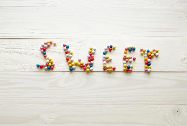 Word sweet gemaakt van kleurrijke ronde snoepjes op witte houten achtergrond