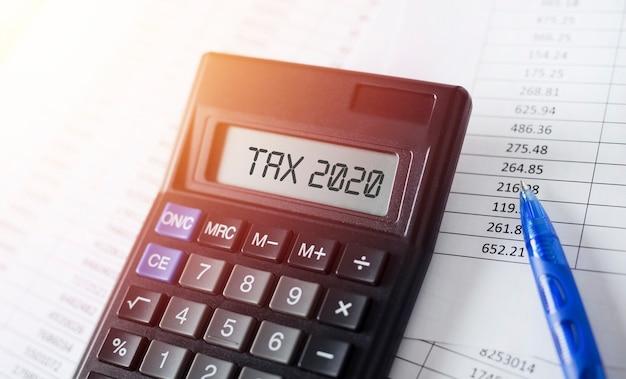 Word tax 2020 op rekenmachine. bedrijfs- en fiscaal concept.