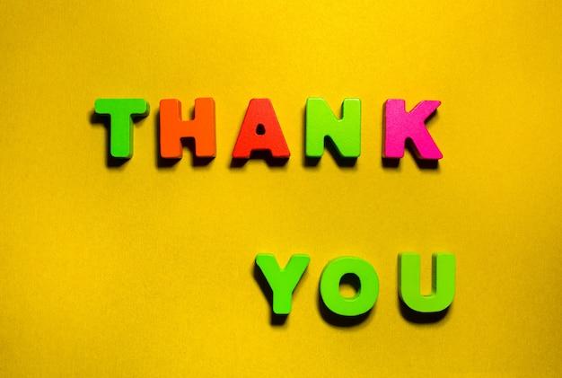 Word-tekst dank u inscriptie door houten letters op geel ambachtelijk papier