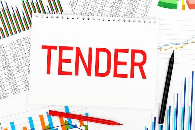 Word tender op notebook, pen, marker, grafiek, diagram op bureau. detailopname. bedrijfsconcept.