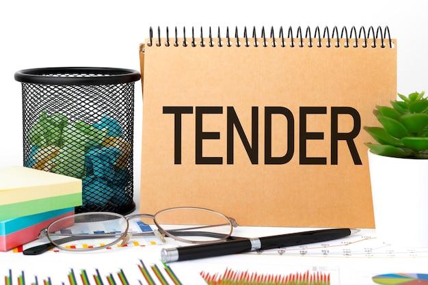 Word tender op notitieboekje, bril, sticker, grafiek, diagram en pen op bureau. bedrijfsconcept.