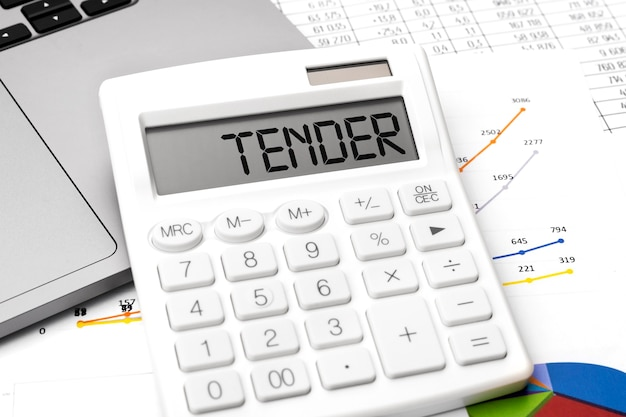 Word tender op rekenmachine, laptop, grafiek, diagram, documenten op bureau. bedrijfsconcept.
