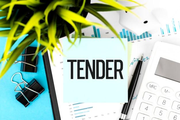 Word tender op sticker, rekenmachine, grafiek, diagram en pen op bureau. detailopname. bedrijfsconcept.
