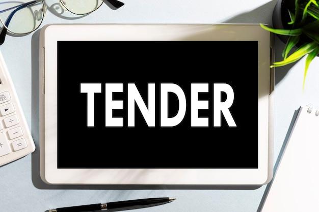 Word tender op tablet, rekenmachine, bril, notitieboekje, pen op bureau. bedrijfsconcept.