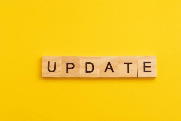 Word update gemaakt van houten letters op gele achtergrond.