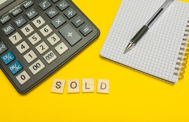 Word verkocht gemaakt met houten letters op gele en moderne rekenmachine met pen en notitieboekje.