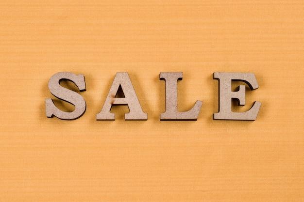 Word verkoop abstracte houten letters, achtergrond gele zijde textuur
