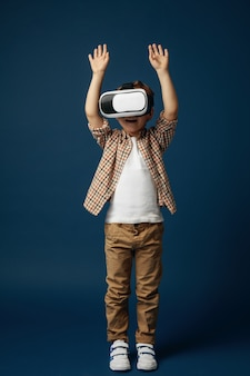 Word verliefd op hi-tech. kleine jongen of kind in jeans en shirt met virtual reality headset bril geïsoleerd op blauwe studio achtergrond. concept van geavanceerde technologie, videogames, innovatie.