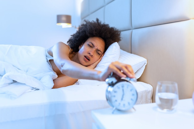 Word wakker van een slapend meisje dat 's ochtends de wekker op het bed stopt.