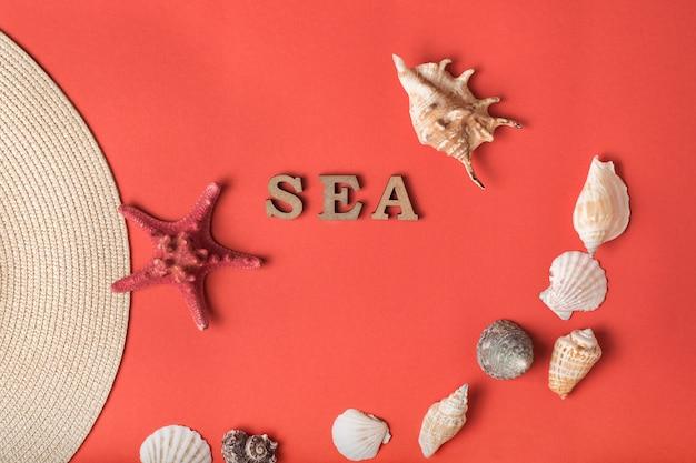 Word zee van houten letters. schelpen, zeesterren en een deel van een hoed. leef koraalmuur. marien concept