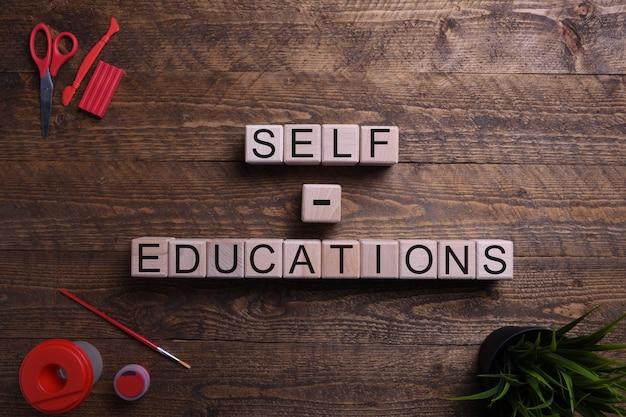 Word zelfonderwijs op houten kubussen, blokken voor wat betreft onderwijs, ontwikkeling en opleiding op een houten lijst. bovenaanzicht.