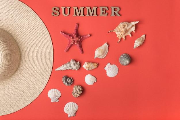 Word zomer van houten letters, schelpen en hoed