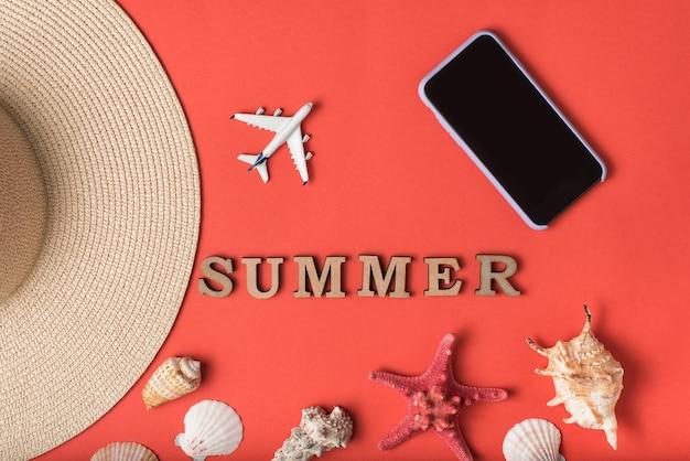 Word zomer van houten letters. schelpen, onderdeel van een hoed, klein vliegtuig en smartphone, live koraalmuur. plat liggen. reizen concept