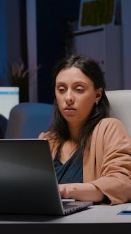 Workaholic ondernemersvrouw die aan een bureautafel zit en financiële afbeeldingen analyseert met behulp van een laptopcomputer