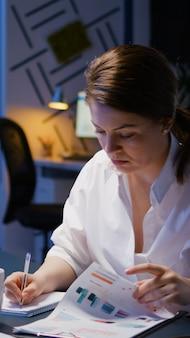 Workaholic zakenvrouw die in de vergaderruimte van het bedrijfskantoor werkt en financiële statistieken schrijft