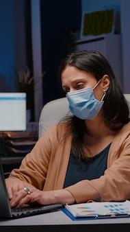 Workaholic zakenvrouw met gezichtsmasker tegen covid werken in startup office