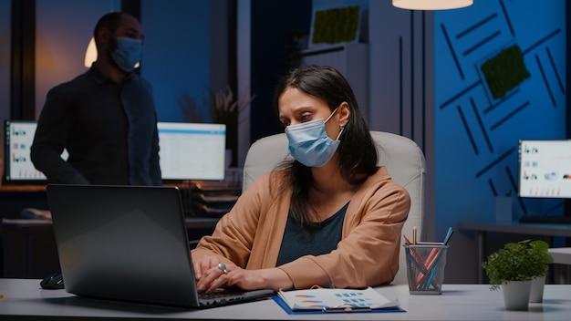 Workaholic zakenvrouw met gezichtsmasker tegen covid19 die in een startup-kantoor werkt en 's avonds laat economische strategie analyseert