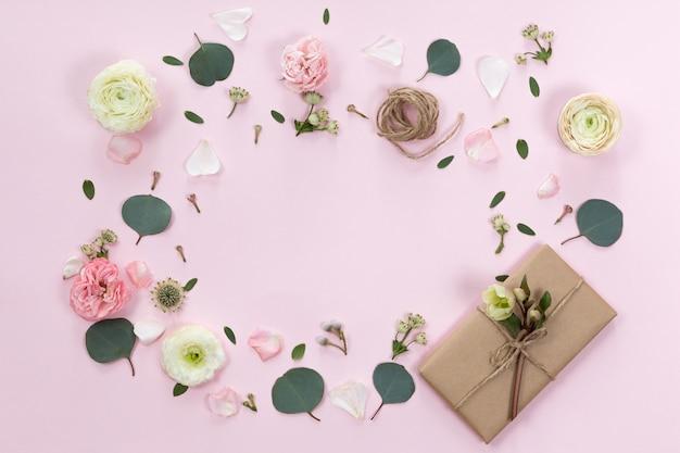 Workspace. geschenk, kopje koffie en roze bloemen. plat lag, bovenaanzicht, kopie ruimte