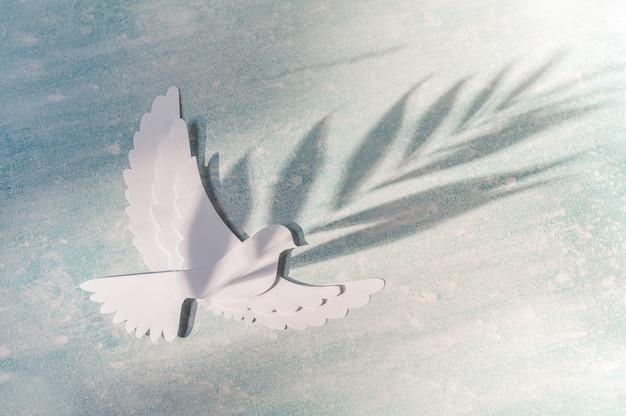 World peace day wenskaartsjabloon. duif die op blauw vliegt.
