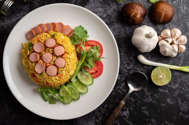 Worst gebakken rijst met tomaten, wortelen en shiitake champignons op het bord