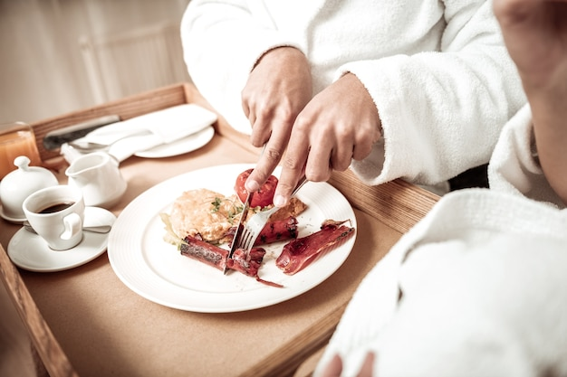 Worst snijden. close-up van man met badjas met mes en vork snijden worst ontbijten