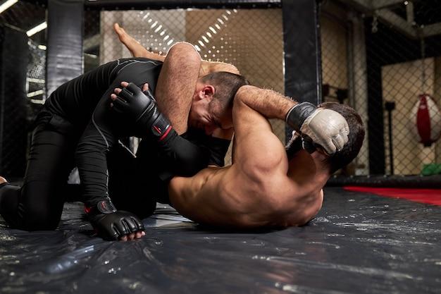 Worstelaarsvechters vechten zonder regels in de achthoek van de ring. shirtloze vechter maakt wurgende ontvangst, gaat winnen, atletische sportieve man tijdens mma