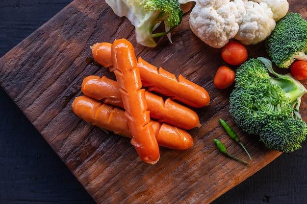 Worsten en groenten op een houten snijplank