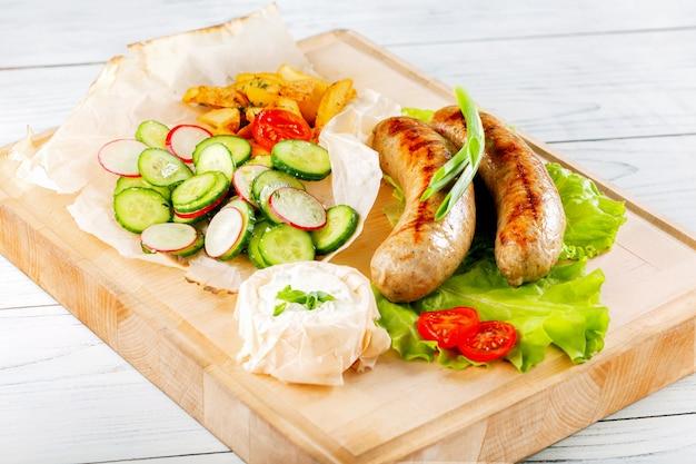 Worsten gebakken met saus en groenten op houten plaat.