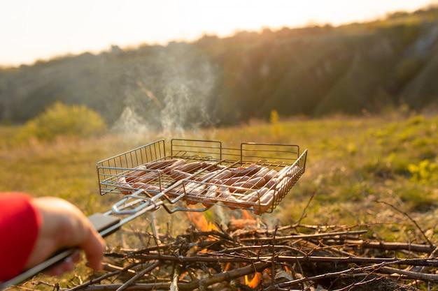 Worsten in de grill op de brandstapel. een picknick in de natuur bij zonsondergang. smaak van de zomer