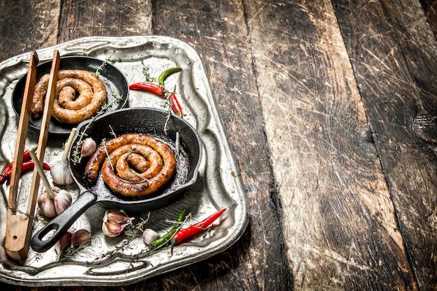 Worsten in pannen op stalen dienblad met hete chilipepers op houten tafel.
