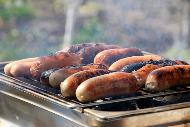 Worstjes, worstjes, worstjes van varkensvlees worden gegrild op een straatgrill, er is rook