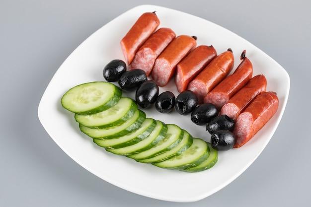 Worststukken met gesneden komkommers en zwarte olijven